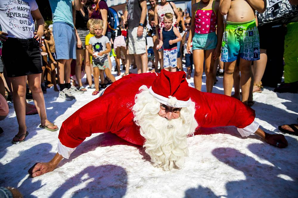 Santa Claus enjoys snow on a hot and sunny day in Best, August 3