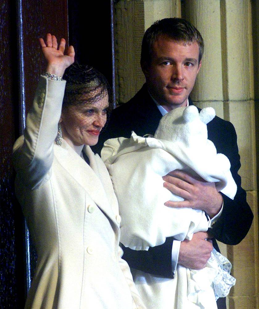 Madonna waves to the crowd as her second husband Guy Ritchie holds their son Rocco after his baptism at Dornoch Cathedral, Scotland, 2000