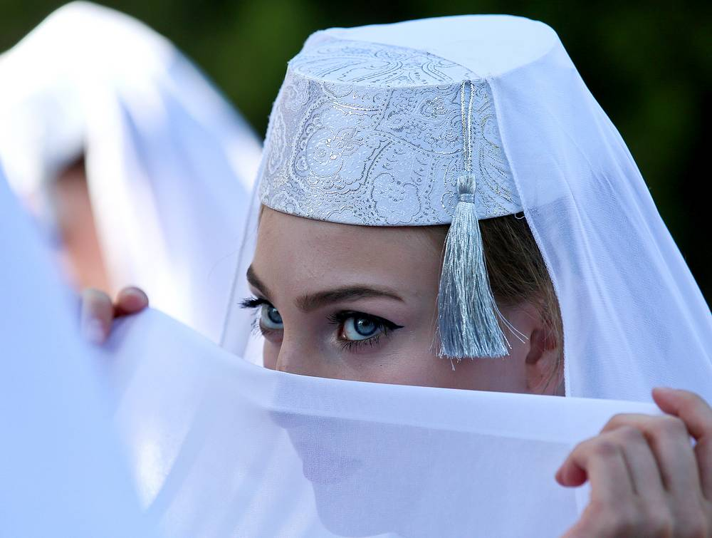 During the holiday, which in most places lasts four days, Muslims slaughter sheep or cattle, distribute part of the meat to the poor and eat the rest. Photo: A girl seen during celebrations of Eid al-Adha in Trenyov Park, Simferopol