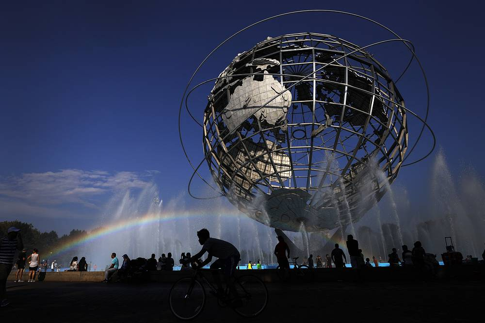 A cyclist passes under a rainbow at the Unisphere fountain inside Flushing Meadows Corona Park outside the US Open tennis tournament in New York, September 3