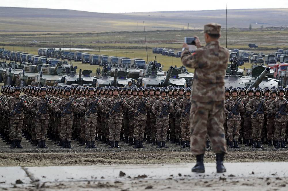 """A Chinese officer takes a photo of Chinese troops as they parade on training ground """"Tsugol"""", about 250 kilometers south-east of the city of Chita during the military exercises Vostok 2018 in Eastern Siberia, September 13"""