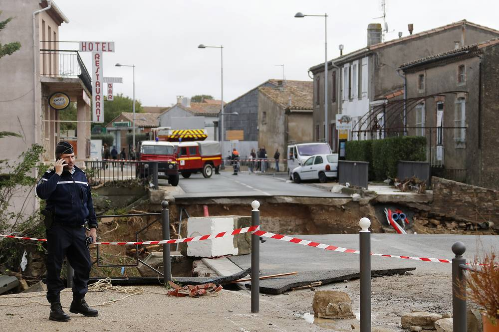A French policeman stands near a collapsed street during rescue operations in the middle of damaged streets in Trebes, France