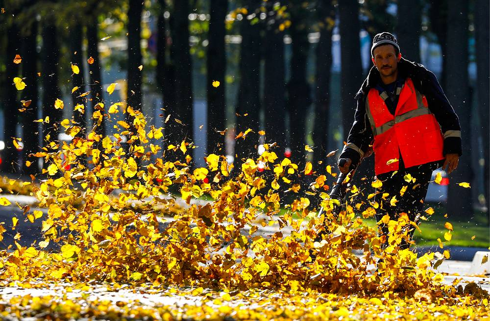 A worker using a leaf blower in street in Moscow