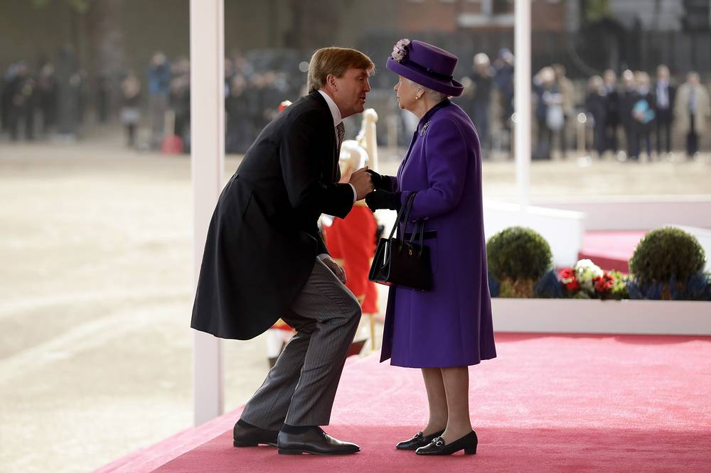 Netherlands' King Willem-Alexander bends down to kiss Britain's Queen Elizabeth II as she greets him upon his arrival to inspect an honour guard during a Ceremonial Welcome on Horse Guards Parade in London, October 23