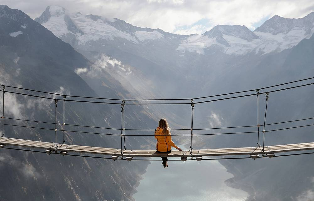 A woman sits on a swing bridge beyond Schlegeis reservoir on a sunny autumn day near the alpine village of Ginzling, October 21