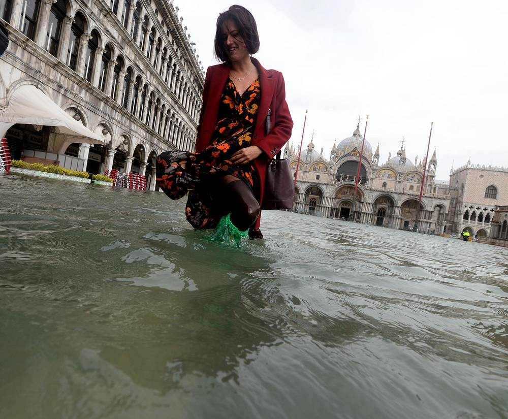 A tourist wanders in high water in Venice, Italy