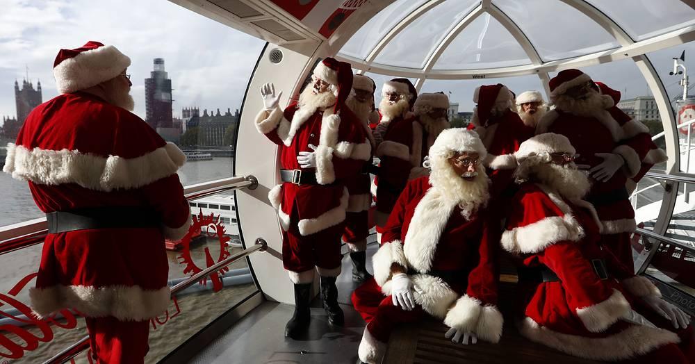 Santas from the Santa School gaze at the London skyline from a pod in the London Eye, November 6