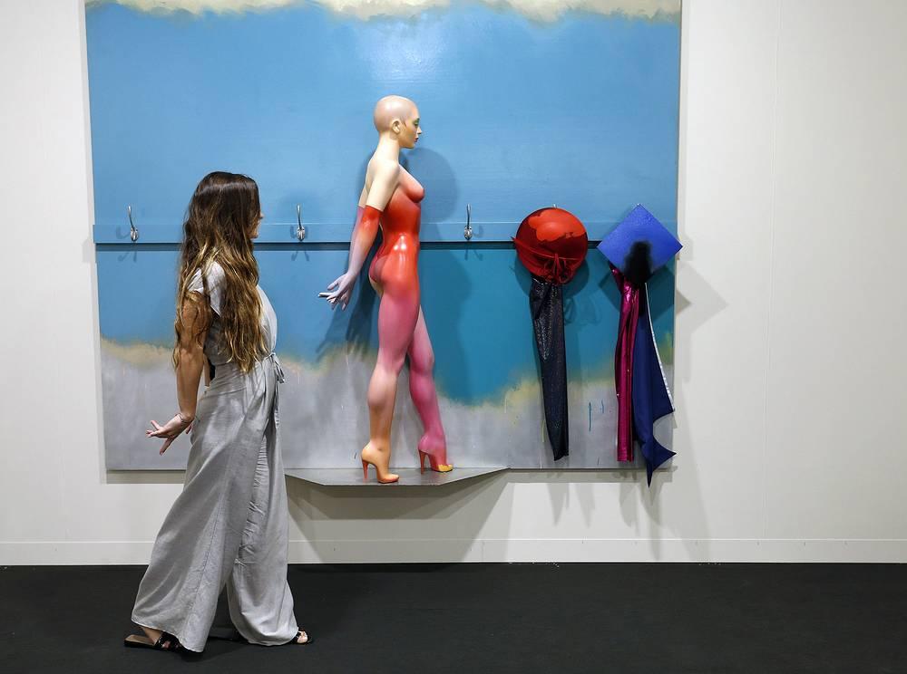 An Art Basel patron poses like a sculpture by artist Allen Jones
