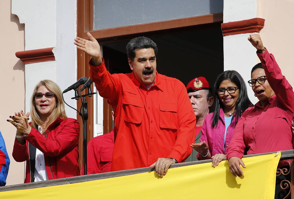 Venezuela's President Nicolas Maduro and first lady Cilia Flores interact with supporters from a balcony at Miraflores presidential palace during a rally in Caracas