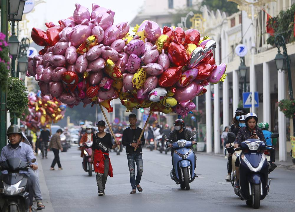 Vendors carry pig-shaped balloons for sale in Hanoi, Vietnam