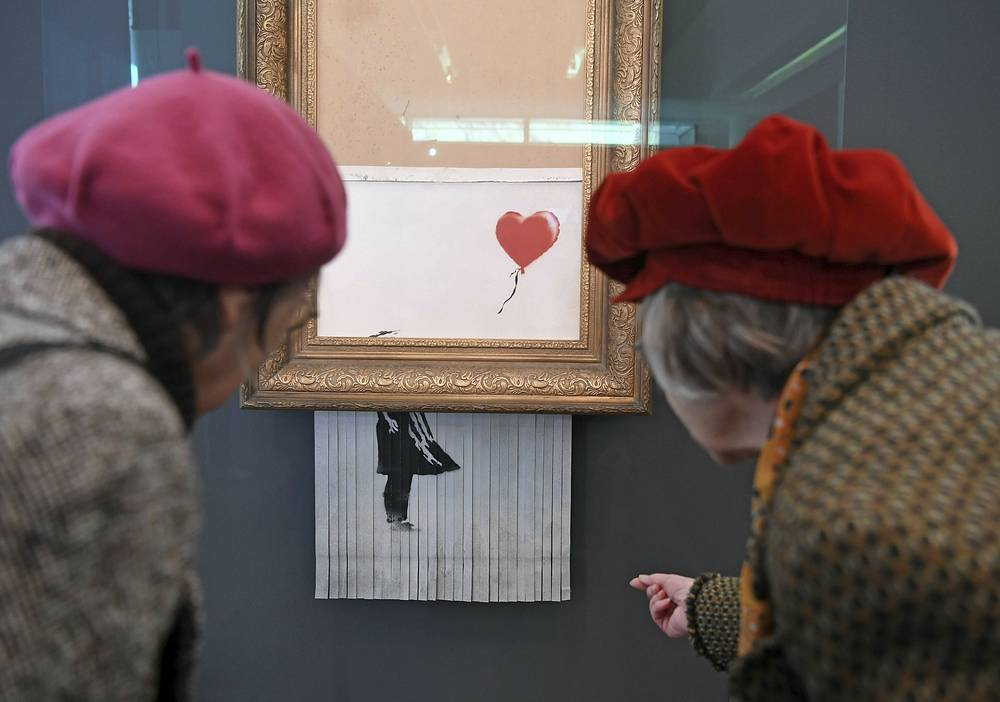 "People look at the shredded Banksy painting ""Love is in the Bin' at the Museum Frieder Burda in Baden-Baden, February 5. It was originally titled 'Girl with Balloon' and since it destroyed itself during an art auction in London, it's called 'Love is in the Bin'"