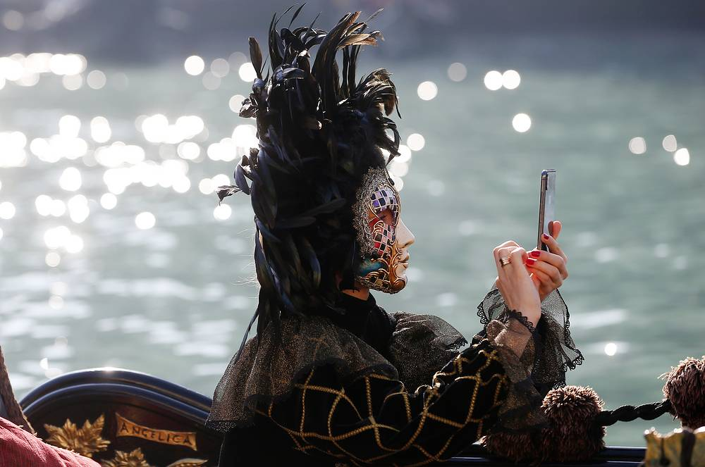 A masked woman checks her smartphone as she sits on a gondola during the water parade in Venice