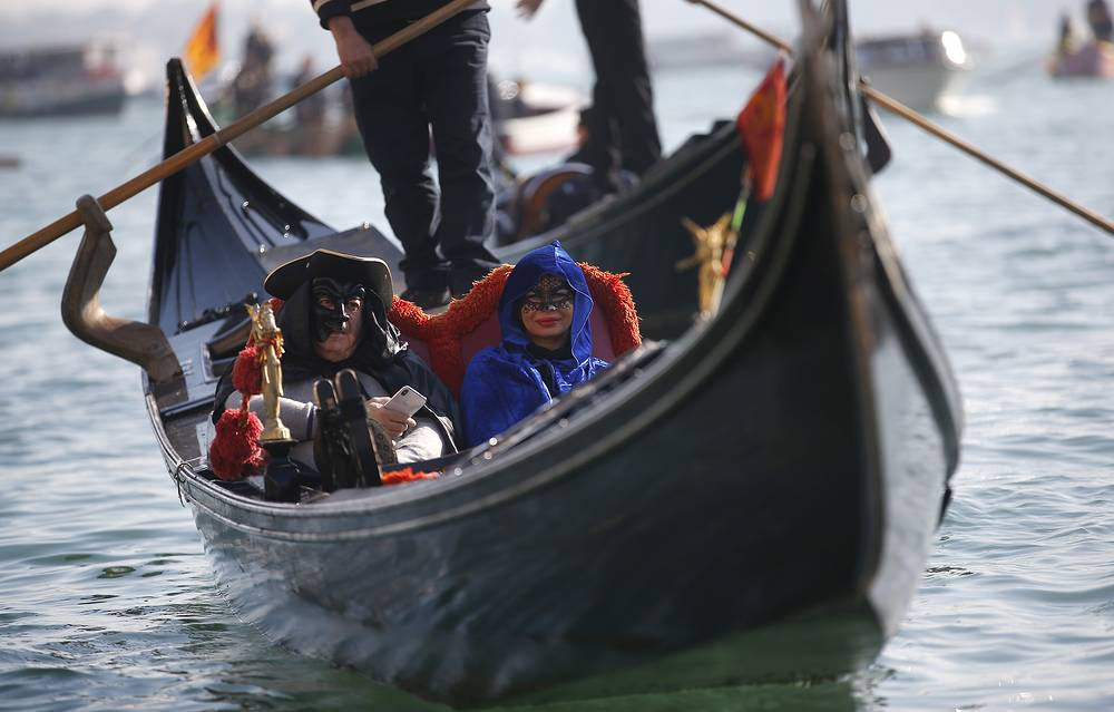 Masked people stand on a gondola during the water parade in Venice