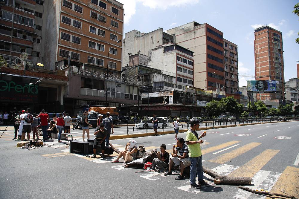 Anti-government demonstrators block a street to protest an electricity blackout in Caracas