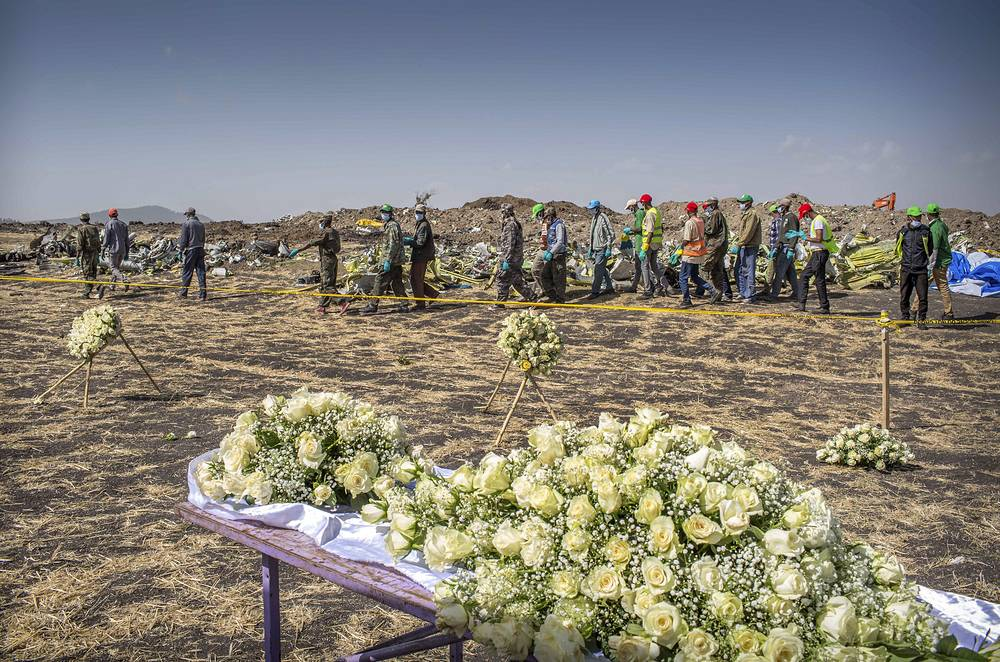 Workers walk past flowers laid at the scene where the Ethiopian Airlines Boeing 737 Max 8 crashed in Ethiopia
