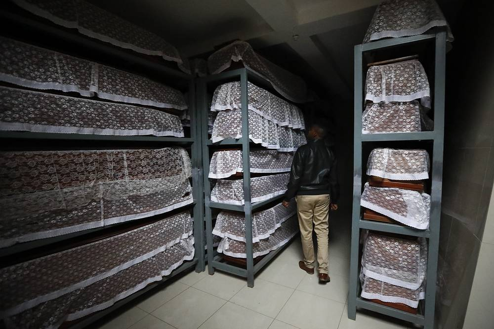 A man looking at caskets containing the remains of the victims of the 1994 genocide in Ntarama, Rwanda