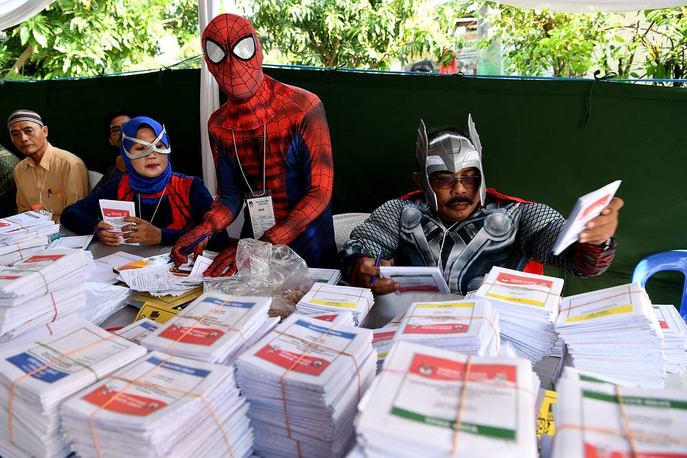 Election officials wearing superhero costumes prepare ballots at a polling station during elections in Surabaya, Indonesia, April 17