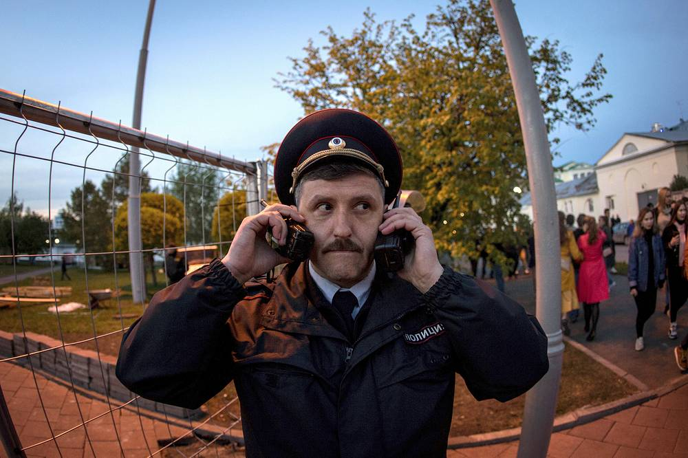 A police officer is seen with two walkie talkies as demonstrators gather to protest plans to construct a cathedral in a park in Yekaterinburg, May 15