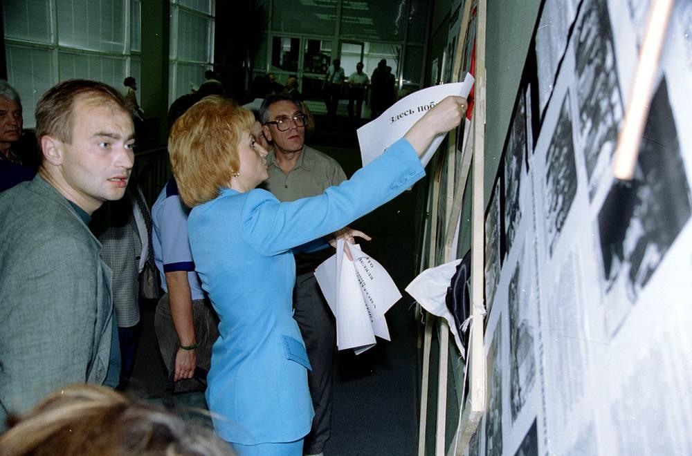 Председатель Думской комиссии по расследованию трагических событий 1993 года Татьяна Астраханкина восстанавливает экспозицию фотовыставки, фотографии с которой сорвала депутат Галина Старовойтова, 1996 г.