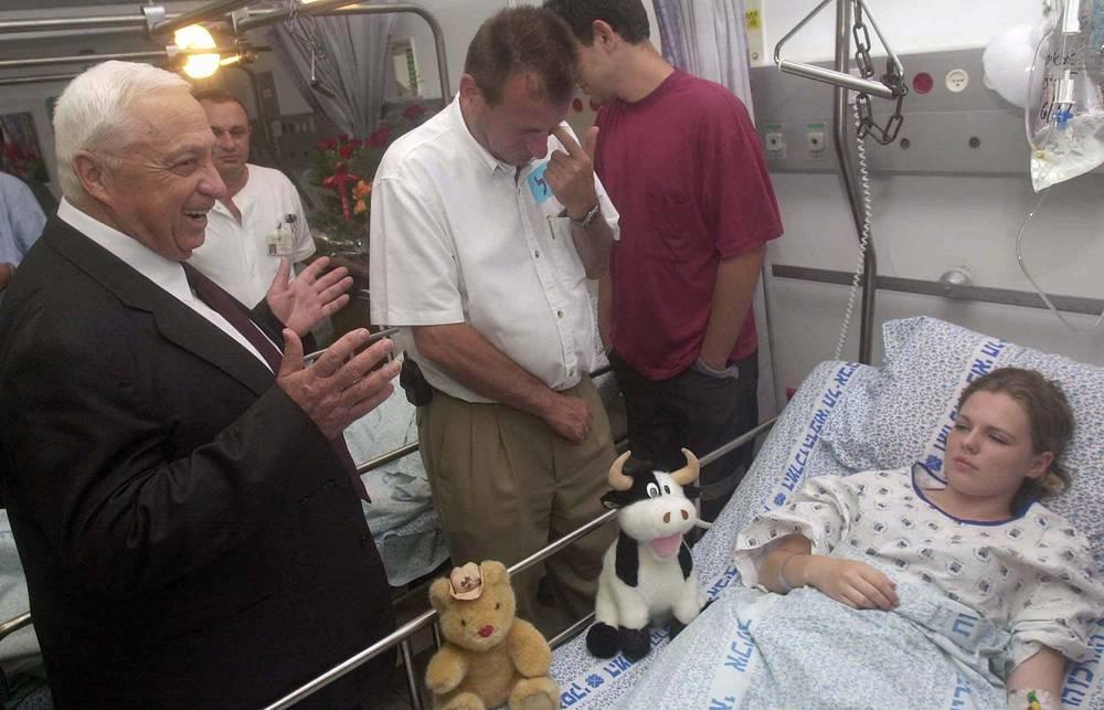 Премьер-министр Израиля Ариэль Шарон посещает пострадавшую в результате взрыва на дискотеке девочку в Тель-Авиве, 3 июня 2001 г.