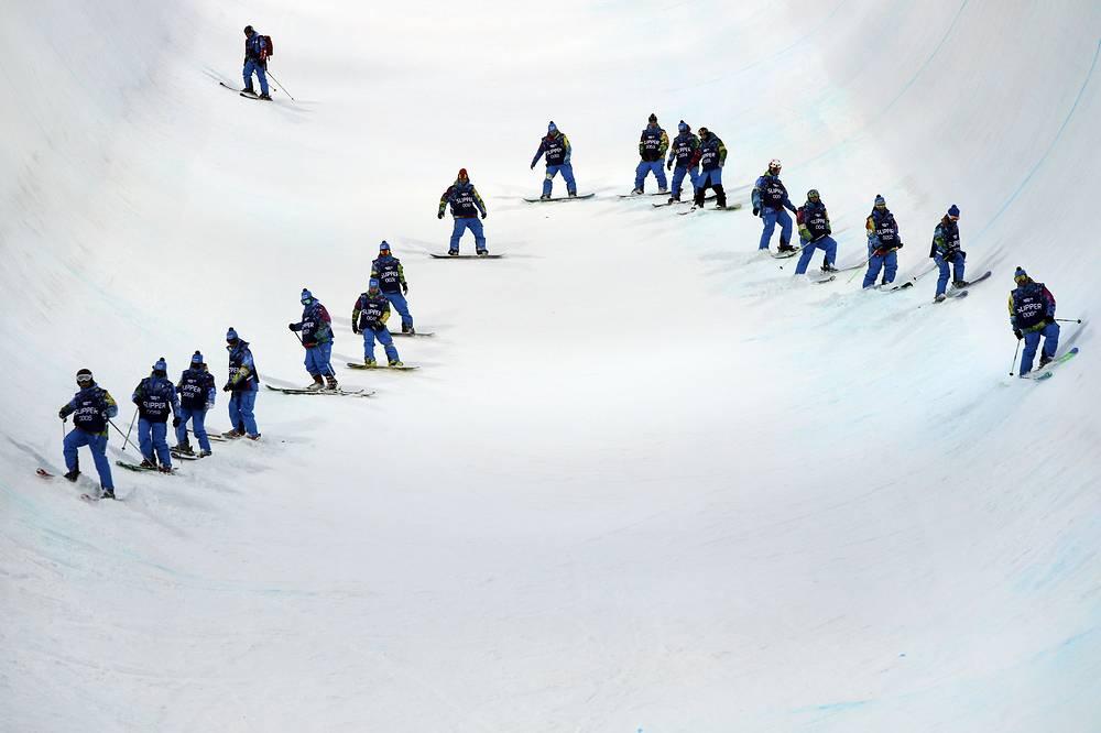 Волонтеры проверяют трассу по сноуборду в экстрим-парке Роза Хутор