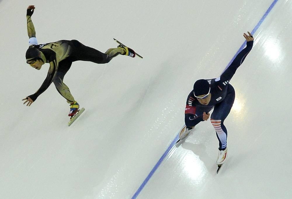 Южнокорейский конькобежецТхэ Бум Мо (справа) и японский конькобежец Дзедзи Като во время забега в олимпийском финале на дистанции 500 м