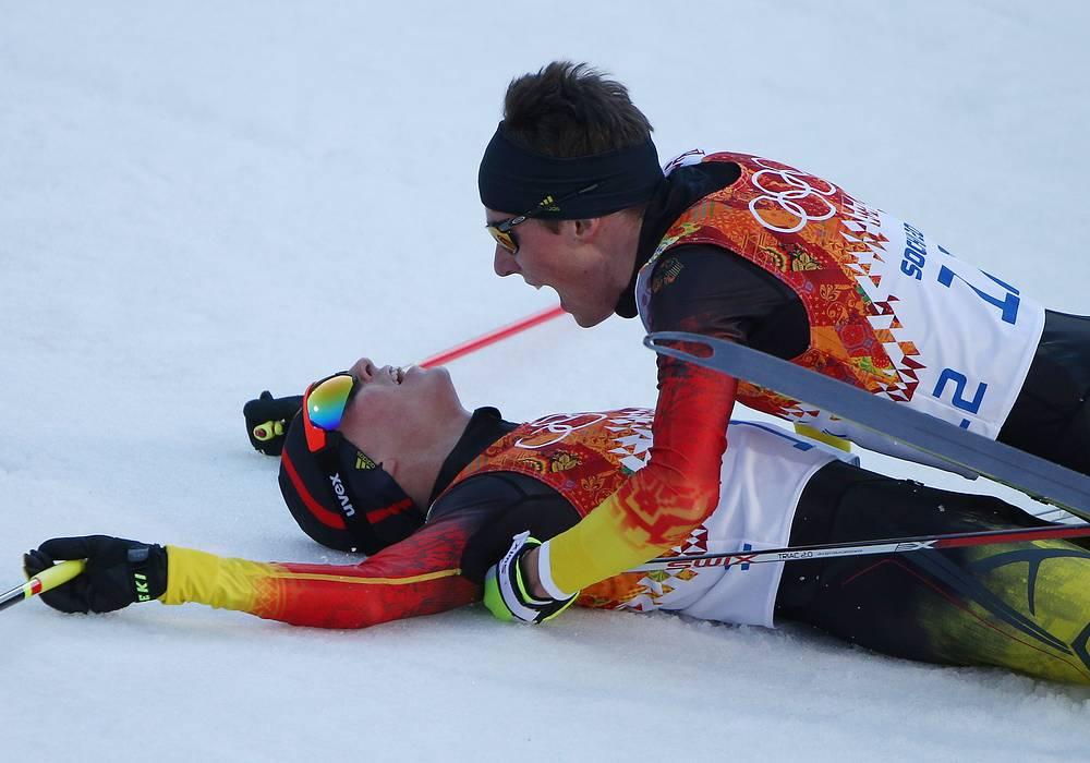 Немецкие спортсмены Эрик Френцель, завоевавший золото, и Йоханнес Ридзек (слева направо) на финише индивидуальной гонки в соревнованиях по лыжному двоеборью