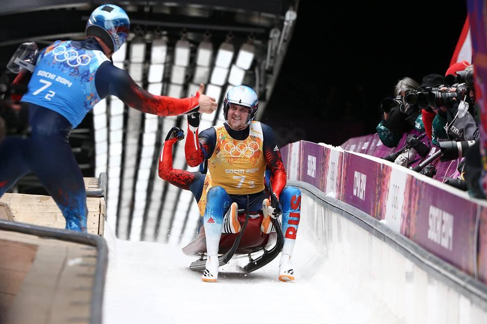 Российские спортсмены Альберт Демченко и Александр Денисьев (слева направо) во время смешанной эстафеты на соревнованиях по санному спорту