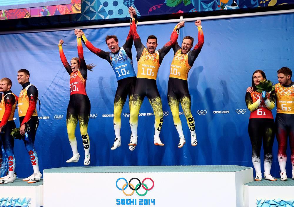 Немецкая сборная по санному спорту во время награждения: Натали Гайзенбергер (слева), Феликс Лох (в синем), Тобиас Вендль, Тобиас Арльт  (справа), выигравшие золотую медаль в эстафете по санному спорту
