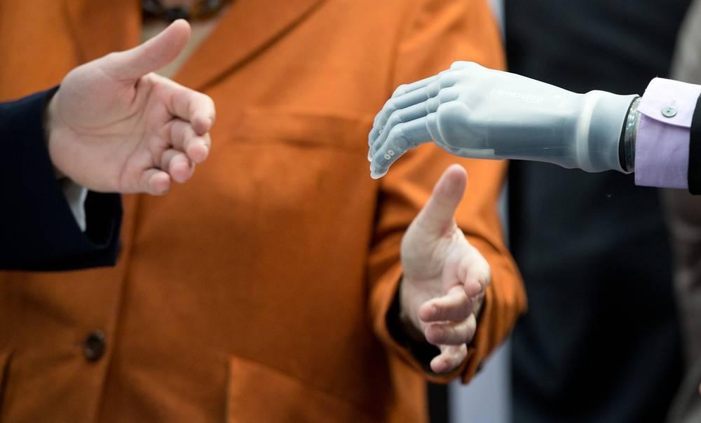 Ангела Меркель и Дэвид Кэмерон протягивают руки бионическому протезу кисти, управляемому с помощью смартфона