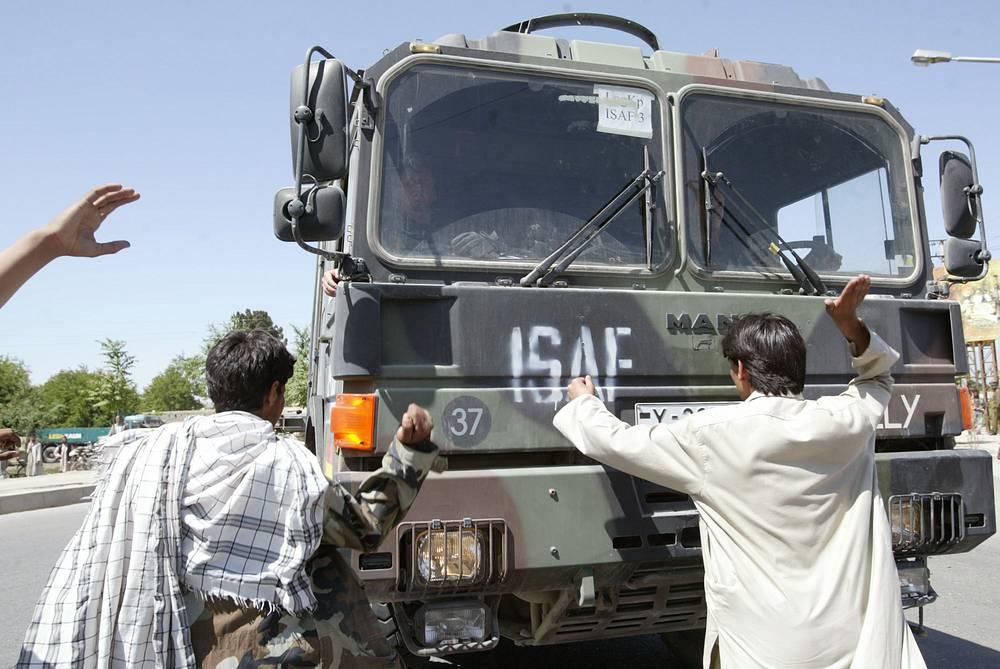НАТО руководит Международными силами безопасности в Афганистане с 2003 года. Студенты университета останавливают грузовик НАТО во время акции протеста против ввода войск НАТО, Кабул, Афганистан, 10 мая 2003 года
