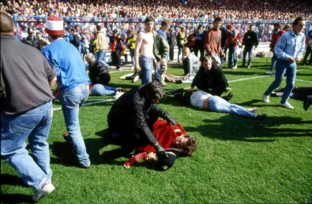 """Матч должен был начаться в 15.00, и многочисленные болельщики не успевали к началу игры. За десять минут до начала матча у входа на стадион собралось большое количество футбольных фанатов, желающих поскорее попасть на трибуны. На фото: стюарды и болельщики помогают пострадавшим во время давки на стадионе """"Хиллсборо"""", 15 апреля 1989 года"""