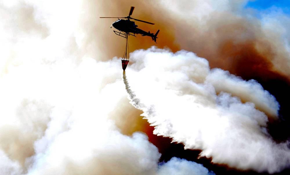 В тушении задействованы по меньшей мере 14 вертолетов и шесть самолетов