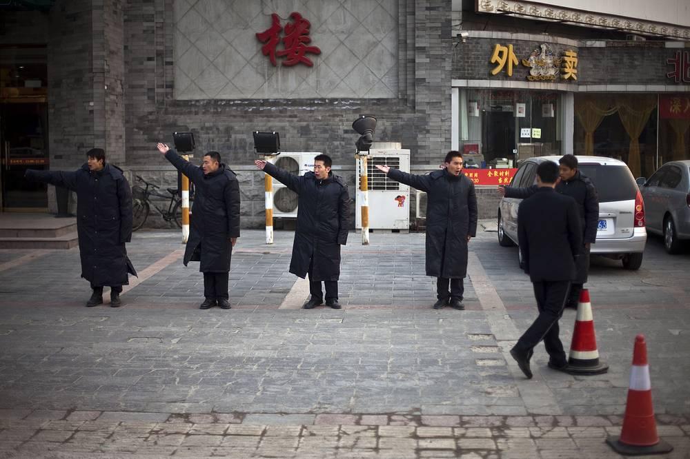 Китай. В Пекине парковки в основном платные, цена часа в районе делового центра составляет 10-15 юаней ($1,6-2,5), время парковки не ограничено. Штраф за неправильную стоянку в среднем 200 юаней. На фото: охранники тренируются жестикулировать, призывая гостей припарковаться, на стоянке у ресторана в центре Пекина