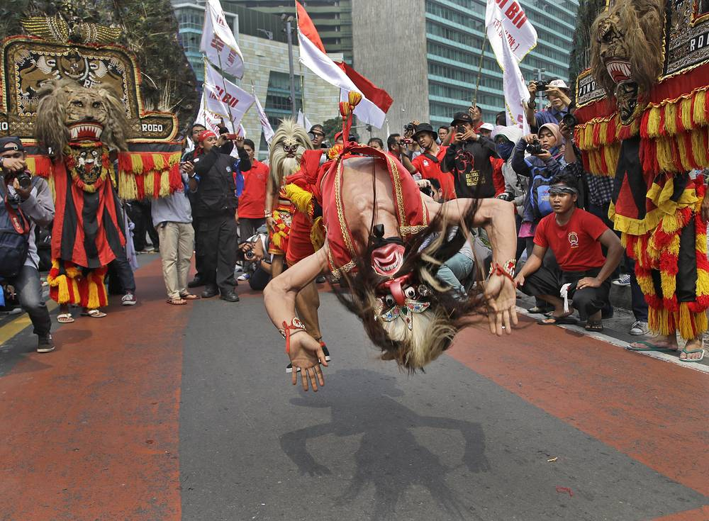 Танцор исполняет сальто во время первомайского шествия в Джакарте