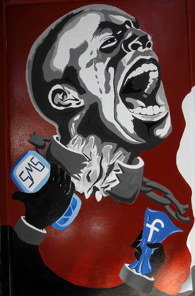 Фреска с изображением человека в кандалах с мобильным телефоном и логотипом Facebook на стене Хелуанской академии художеств, посвященная свержению Хосни Мубарака и египетской революции