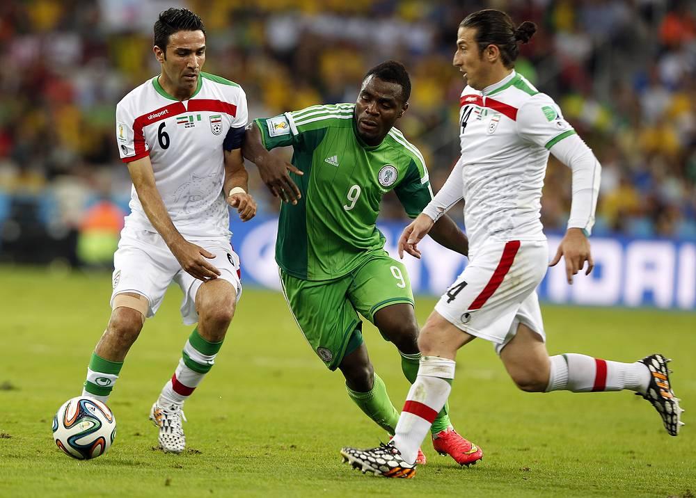 Нигерийский нападающий Эммануэль Эменике в борьбе с иранскими игроками