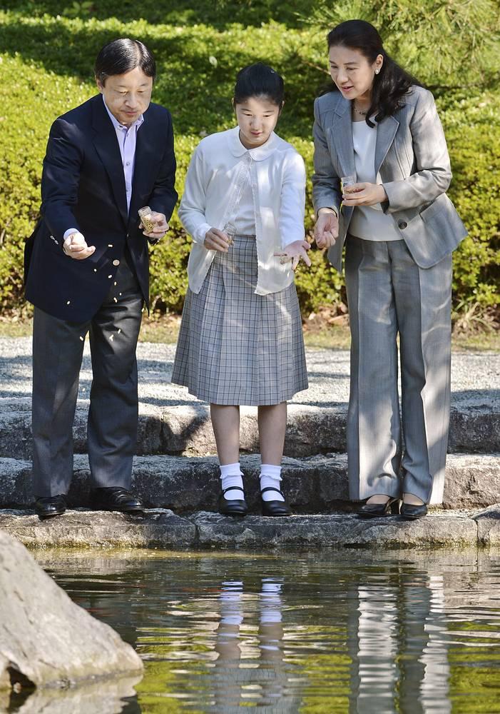 Наследный принц Японии Нарухито, кронпринцесса Масако и их дочь принцесса Айко кормят карпов в пруду парка Шиосай во время небольшого отпуска, 2012 год