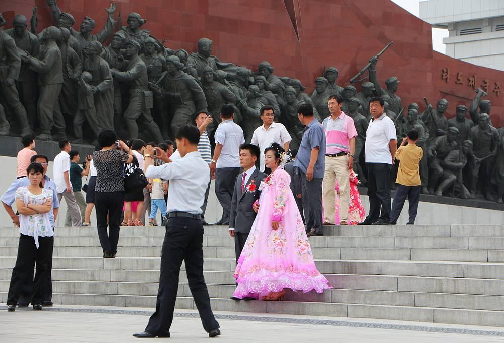 """Участники свадебной церемонии фотографируются на фоне """"Большого монумента"""" на холме Мансудэ"""