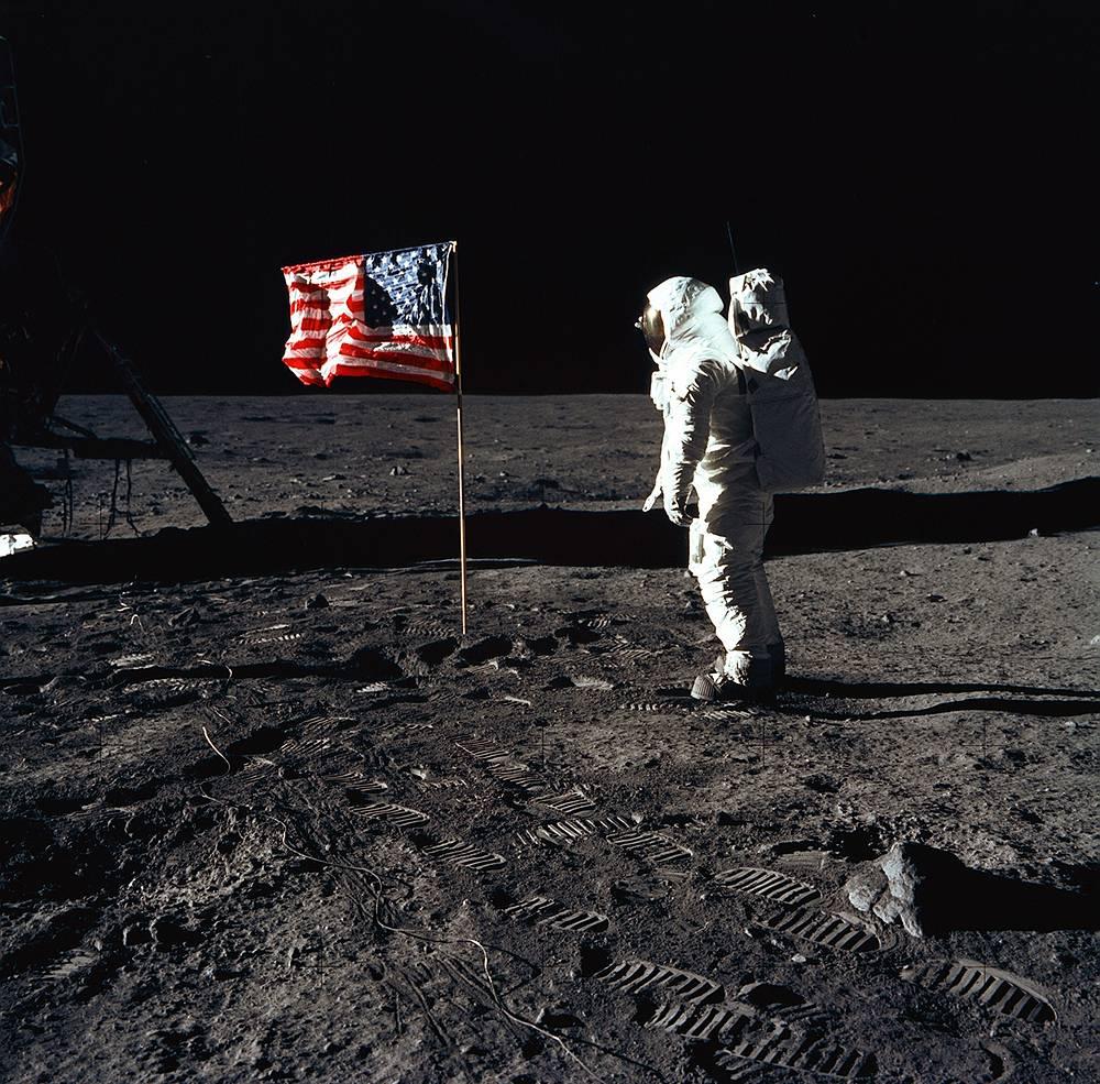 Пилот лунного модуля Эдвин Олдрин позирует для фотографии рядом с американским флагом во время миссии на поверхности Луны