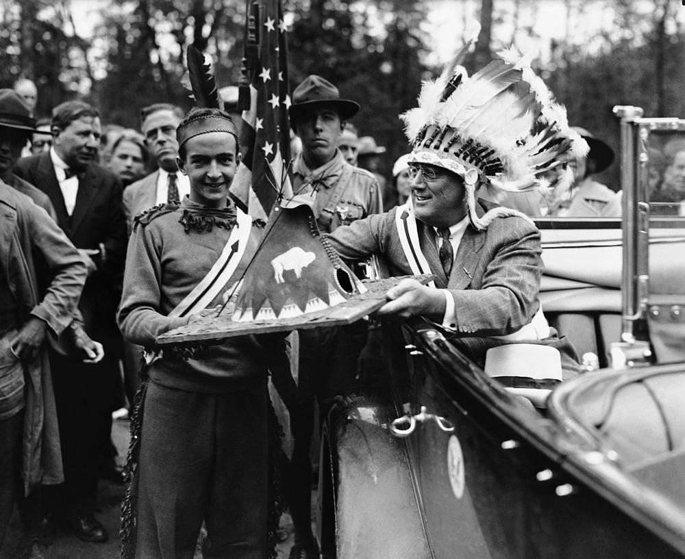 Президент США Франклин Рузвельт в военном головном уборе индейцев. В подарок Рузвельт получает миниатюрный вигвам, 1933 год