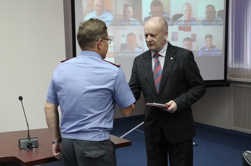 Вице-губернатор Томской области Вячеслав Семенченко вручает награду полицейскому