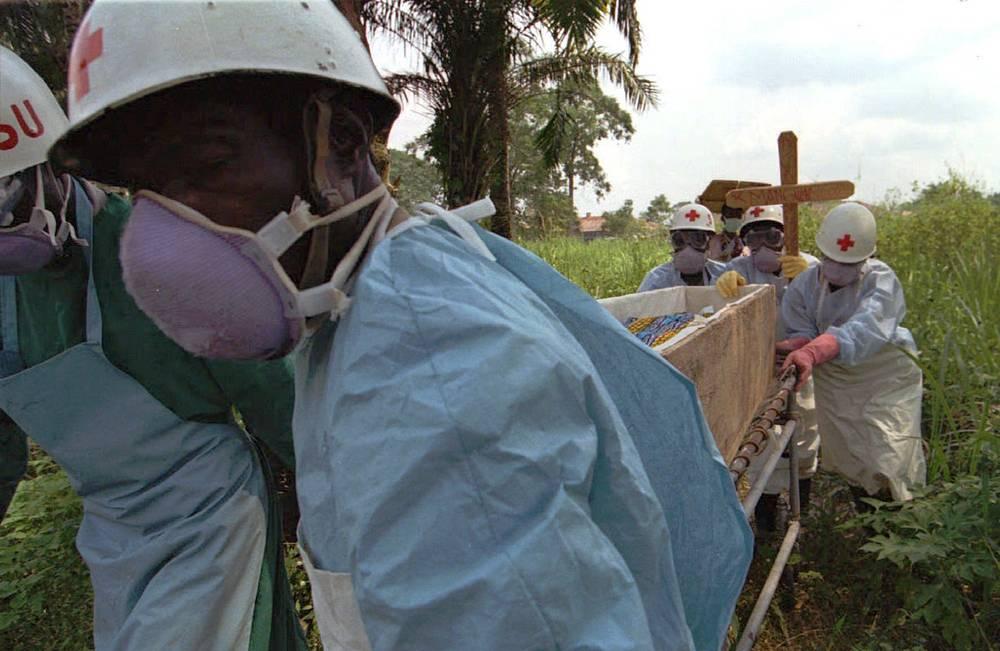 До 90% случаев заболевания заканчиваются летальным исходом. На фото: врачи Красного Креста ДР Конго перевозят тела погибших от лихорадки Эбола в городе Киквит, 1995 год