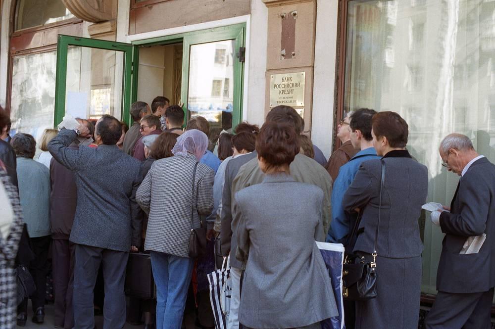 """По расчетам Московского банковского союза, потери экономики России от кризиса в августе 1998 года составили $96 млрд. Из них корпоративный сектор потерял более $30 млрд, население - $19 млрд. На фото: вкладчики у здания банка """"Российский кредит"""", 1998 год"""