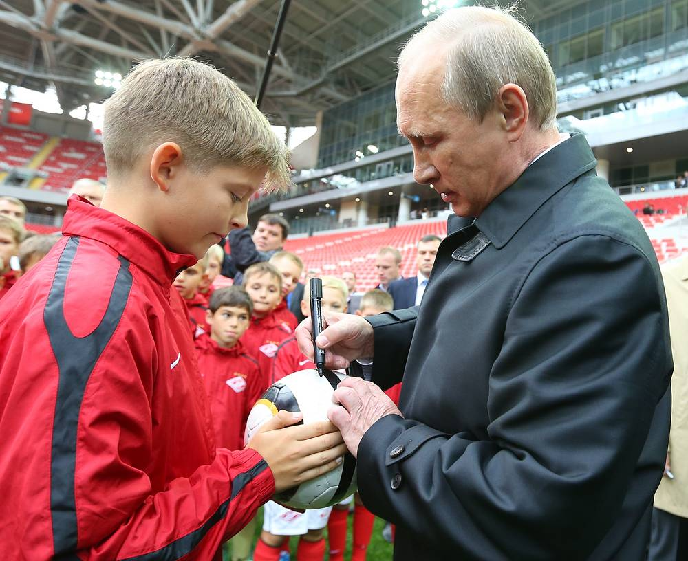 Владимир Путин дает автограф на мяче