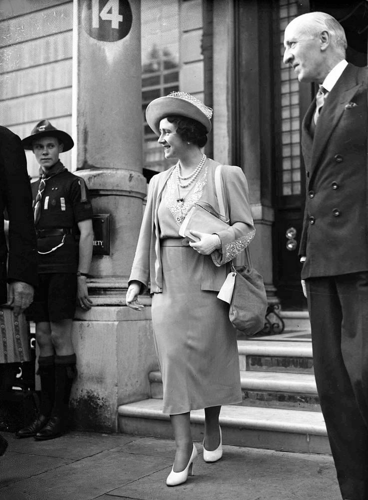 Королева-консорт Великобритании Елизавета с противогазом покидает штаб-квартиру Красного Креста в Лондоне. 5 сентября 1939 года