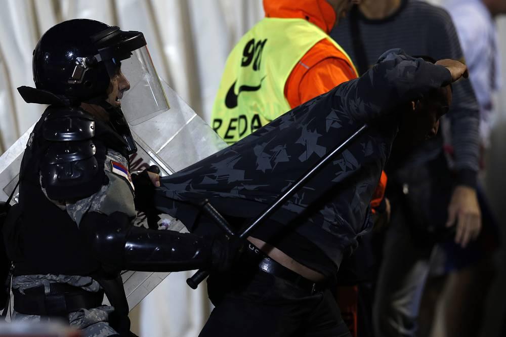 Сербский полицейский производит задержание местного фаната
