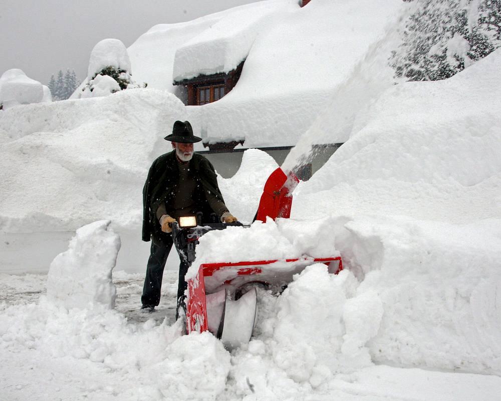 Местный житель расчищает улицу от снега в одном из австрийских городов, 2010 год