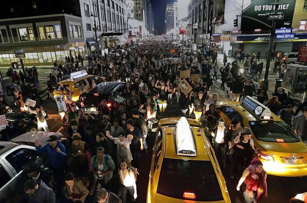 Акции протеста проходят не только в Фергюсоне - тысячи людей вышли на улицы Нью-Йорка, Лос-Анджелеса, Окленда и других городов. На фото: протестующие на Пятой авеню в Нью-Йорке