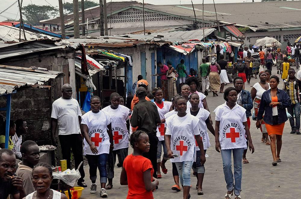 Вспышка распространилась на пять стран - Гвинею, Либерию, Сьерра-Леоне, Нигерию и Сенегал. На фото: врачи Красного Креста во время работы в Либерии
